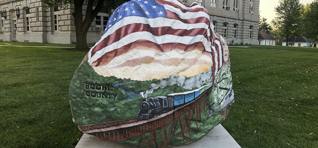 The front of the Boone County Freedom Rock features a train chugging across the Kate Shelley Bridge, draped by an American flag.